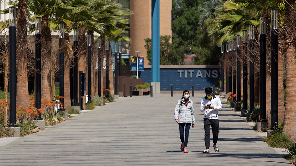Two students wearing face masks walks on Cal State Fullerton campus promenade