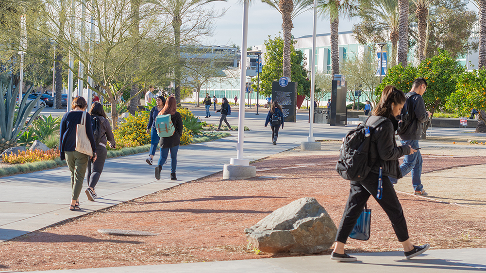 a few students walking around the front of Cal State Fullerton's campus