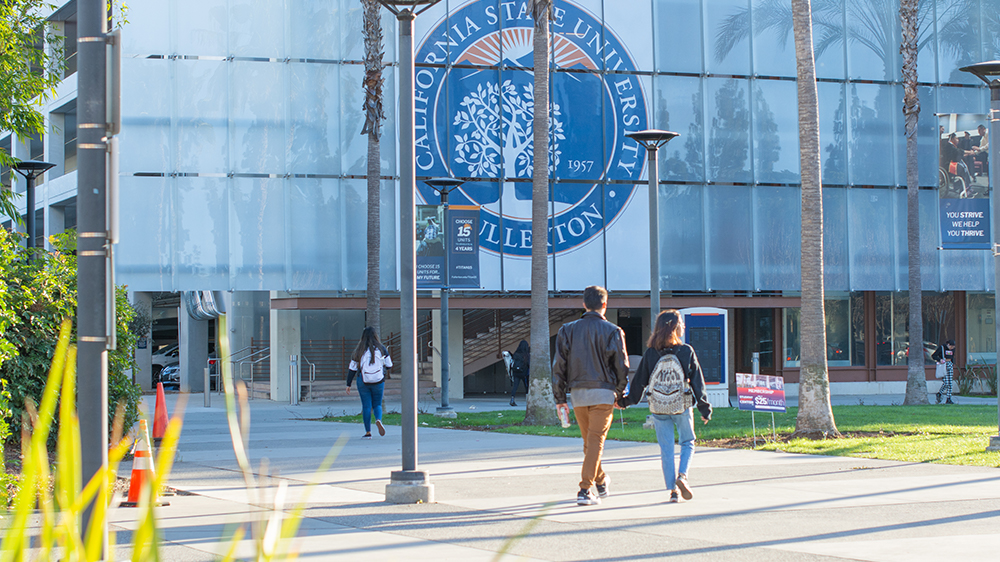 Students walking on Cal State Fullerton campus holding hands