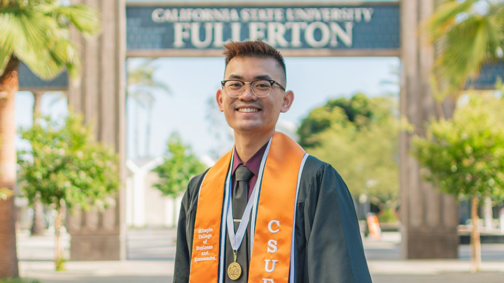 Brandon Sayphraraj, in graduation fatigues, in front of the Titan sign at Cal State Fullerton