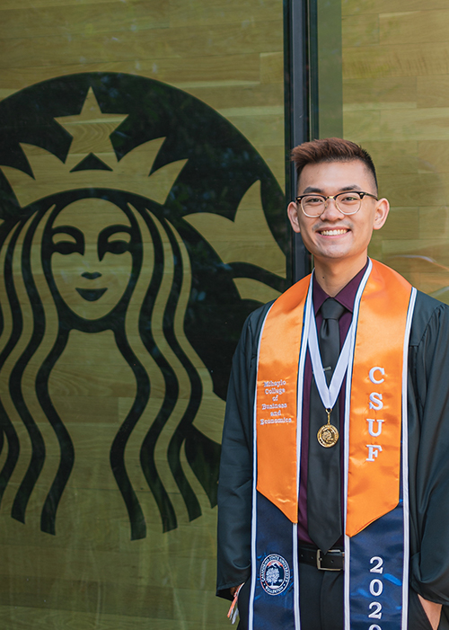 Brandon Sayphraraj stands in front of the Starbucks logo at Cal State Fullerton