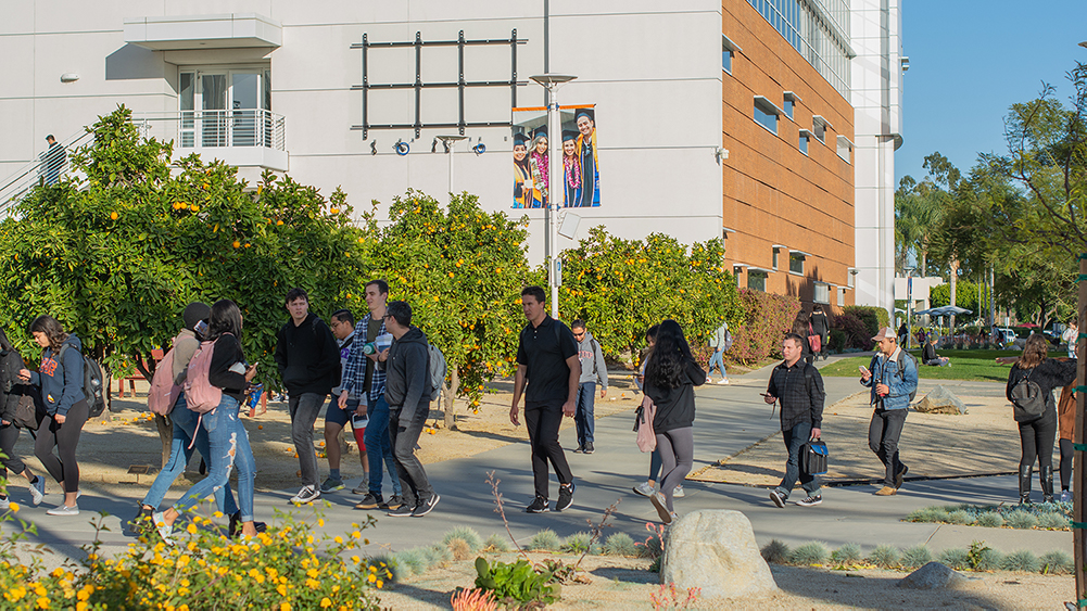 Students walk in front of Mihaylo Hall at Cal State Fullerton prior to the COVID-19 pandemic