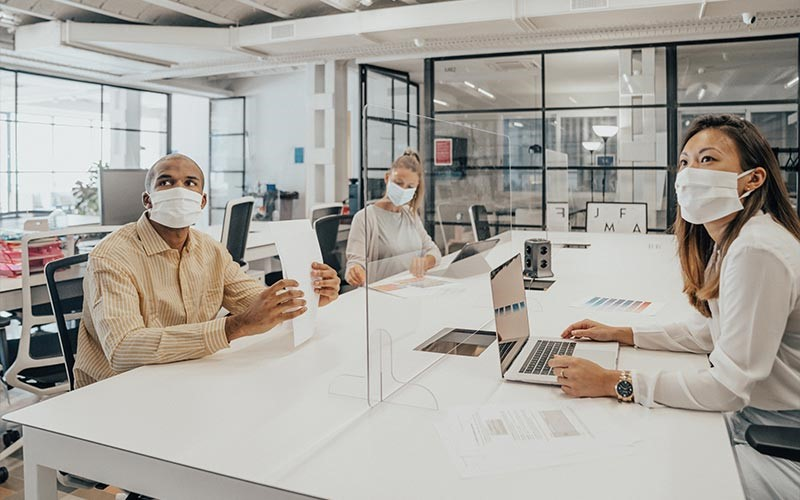 Workers wear personal protective equipment at an office during the coronavirus pandemic