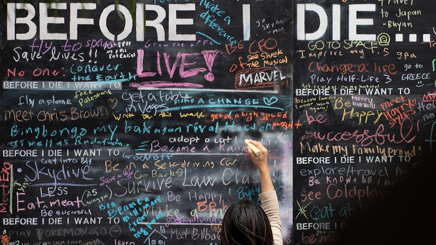 student writing on the Before I Die wall