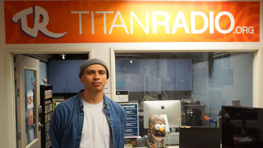 Landy Waight stands in front of the Titan Radio sign