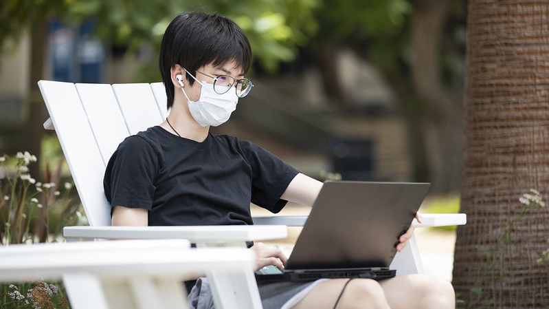 student looking at open laptop screen on campus