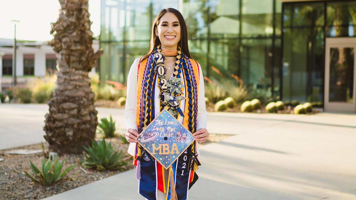 Ari Leon holds a graduation cap noting her MBA achievement in front of Titan Student Union at Cal State Fullerton