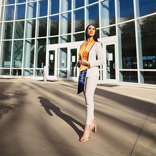Ari Leon poses in professional attire and graduation sash in the courtyard of Steven G. Mihaylo Hall at Cal State Fullerton