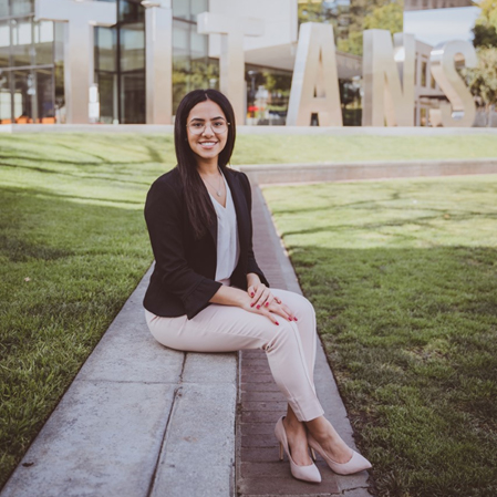 Selene Hanna, dressed in professional business attire, sits in front of the Titan sign at the Titan Student Union at Cal State Fullerton