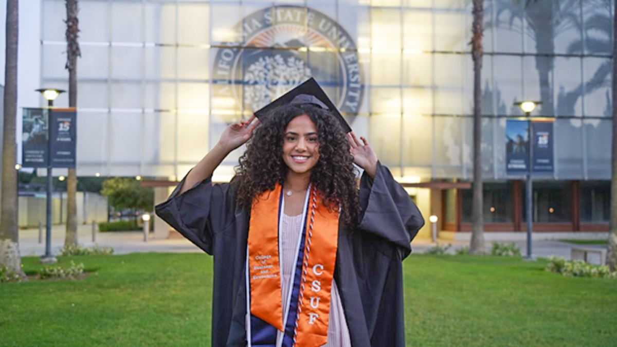 Selene Hanna poses in cap and gown in front of the Nutwood Parking Structure at Cal State Fullerton