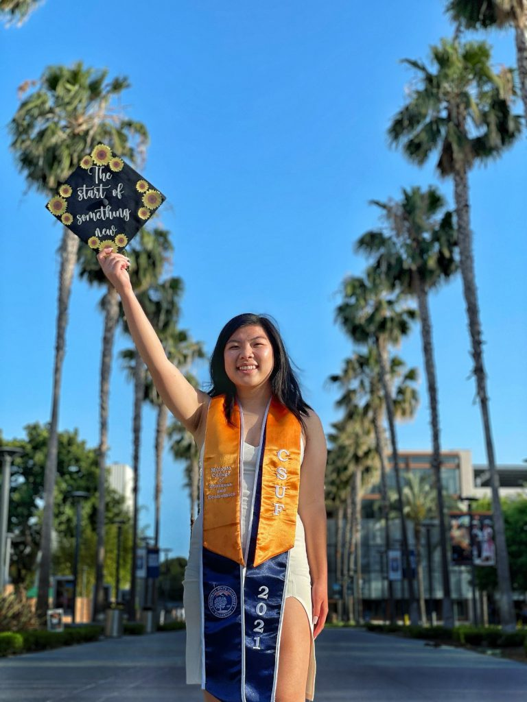 Kathy Au'21 on the campus of Cal State Fullerton in cap and gown