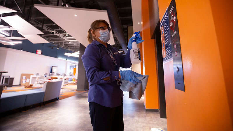 A woman sanitizes the Pollak Library at Cal State Fullerton during COVID